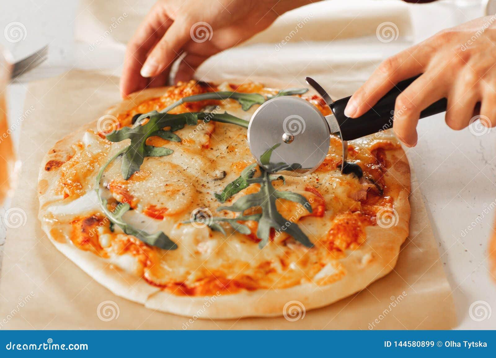 Kvinnans hand med en kniv klippte pizza på den vita bakgrundsnärbilden