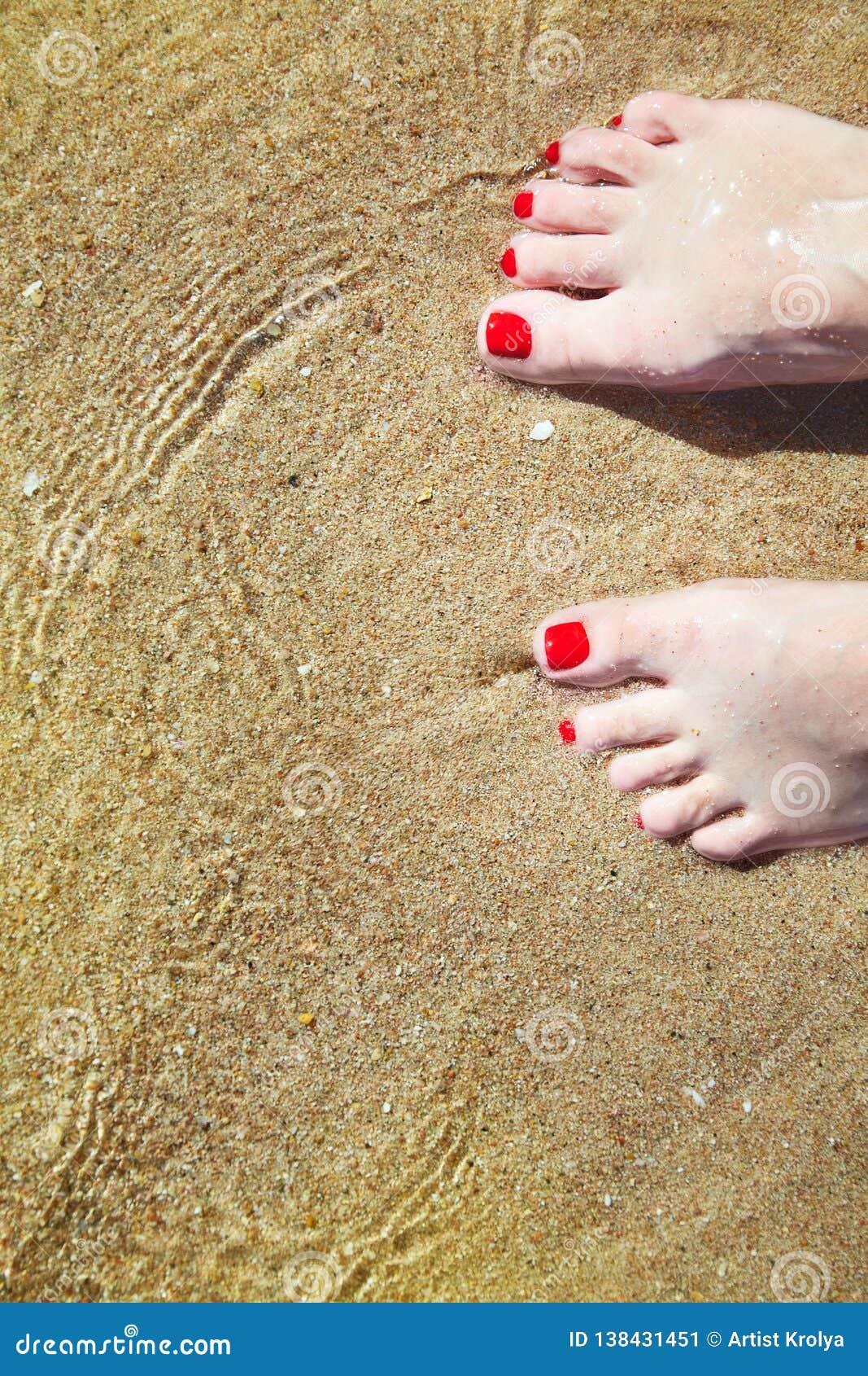 Kvinnans spikar pedicured fot med rött polermedel på tår i sanden i vatten