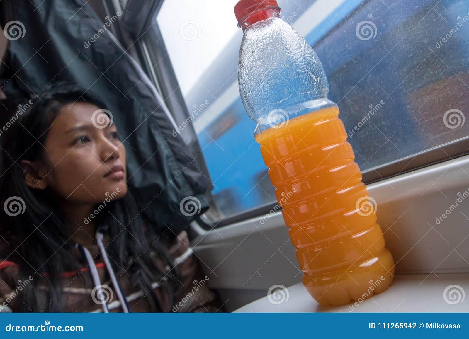Kvinnaridning vid järnvägen med orange fruktsaft på tabellen
