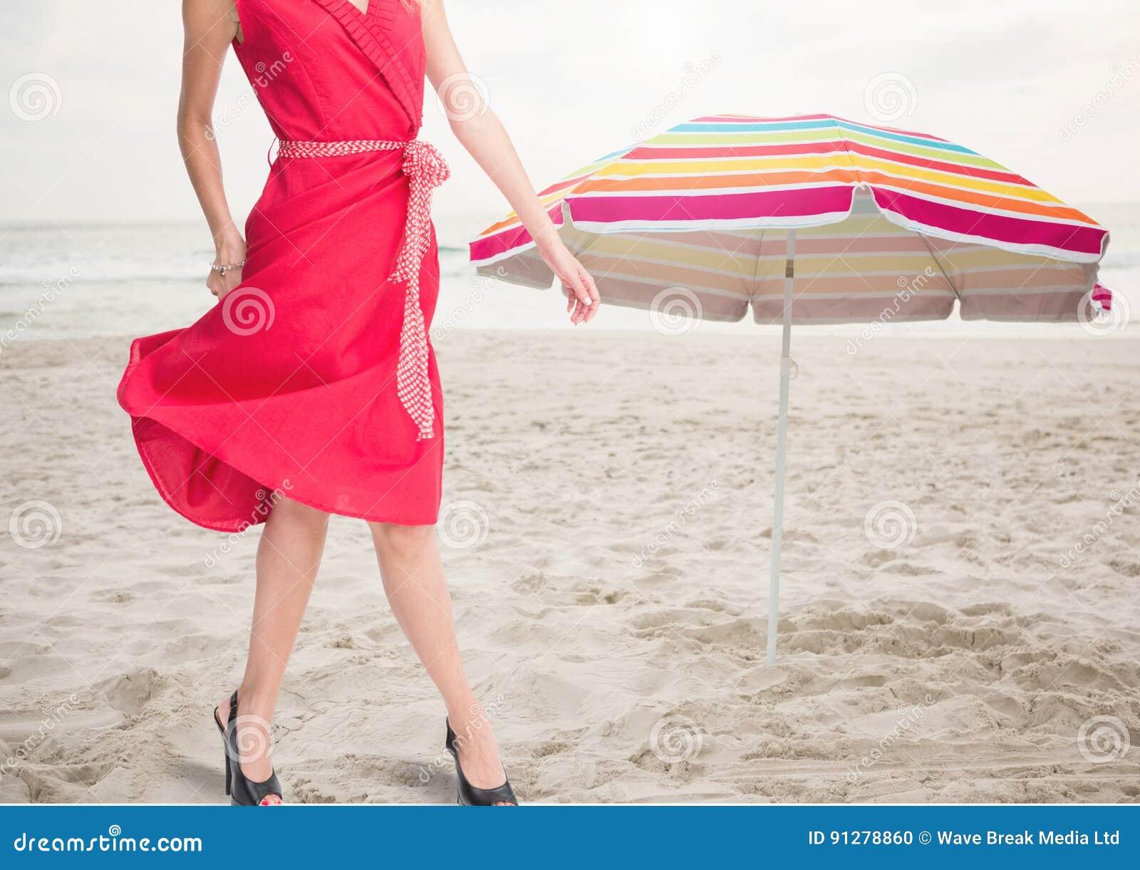 Kvinnas ben som står på stranden vid paraplyet