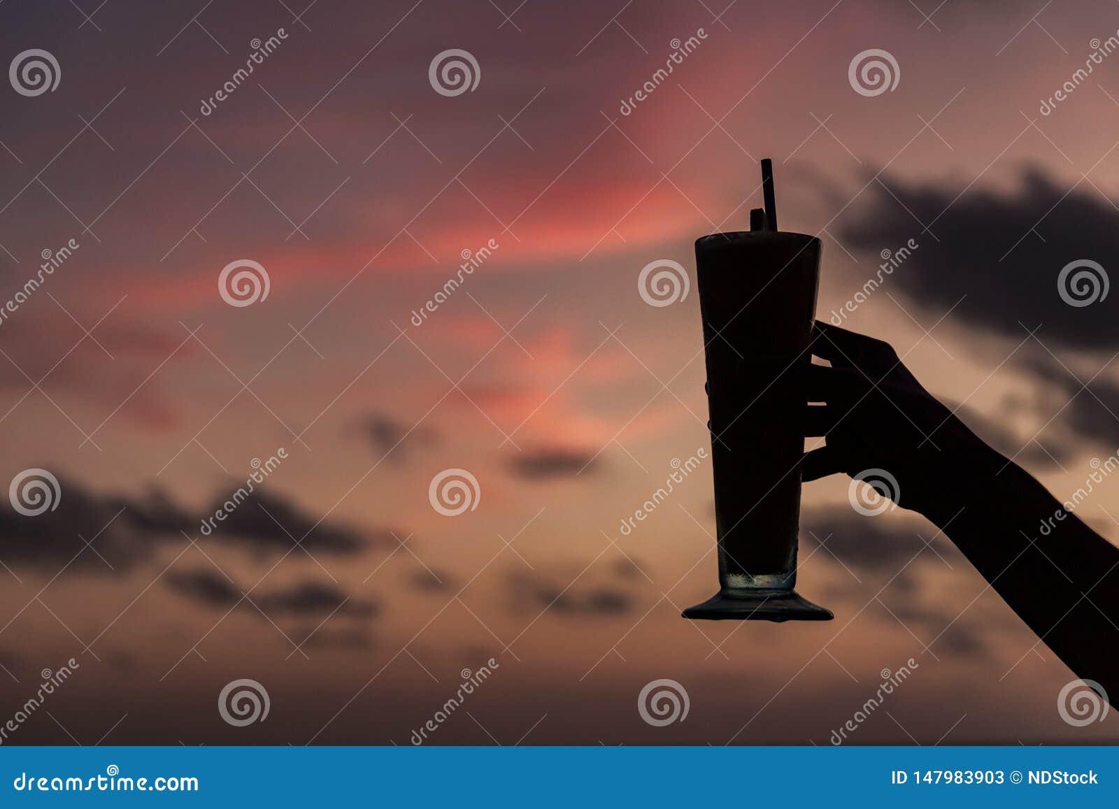 Kvinnas hand som rymmer en coctail mot solnedgången Lycklig timme