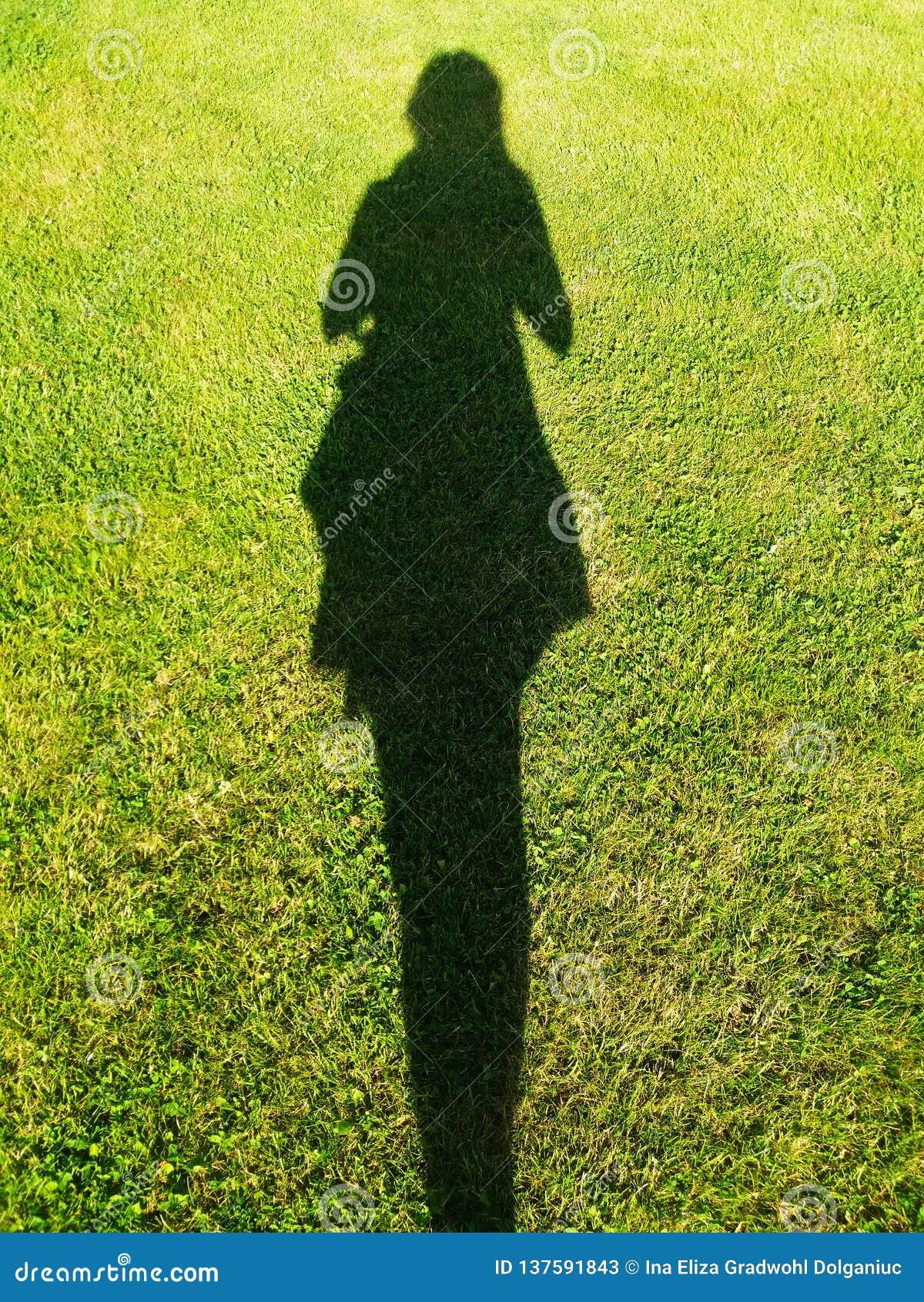 Kvinnas skugga på gräset