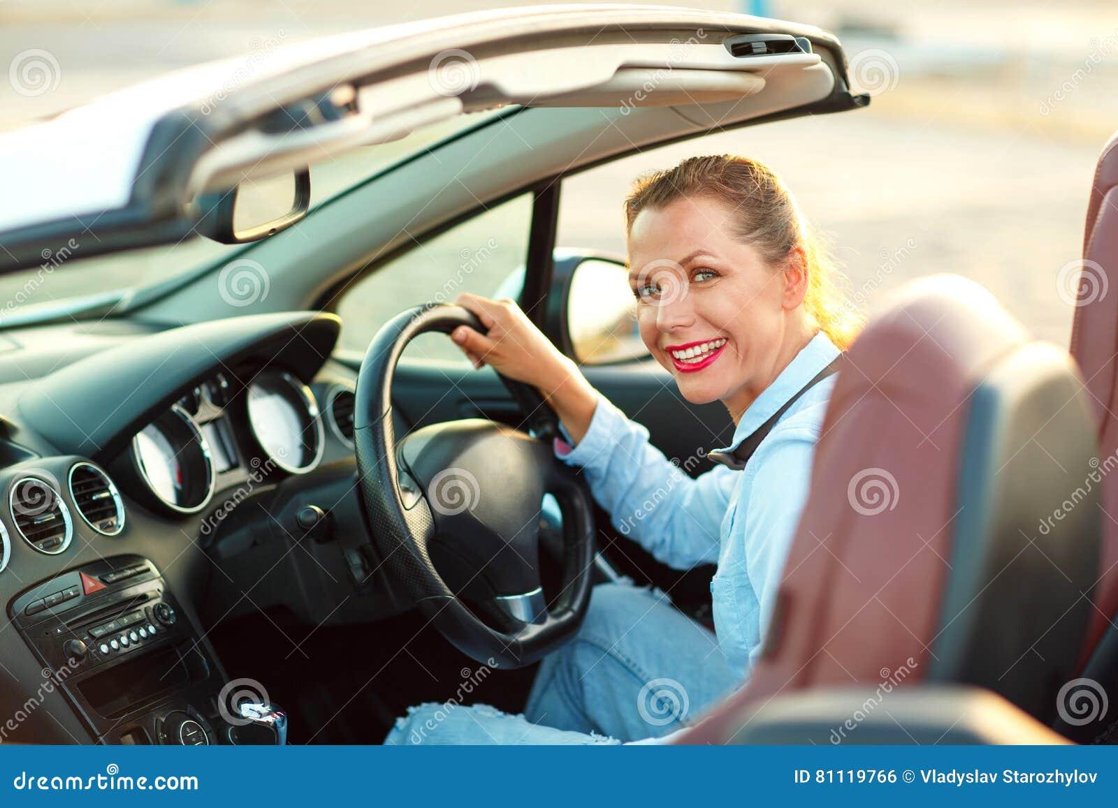 Kvinnasammanträde i ett konvertibelt bil- begrepp av att köpa en använd ca