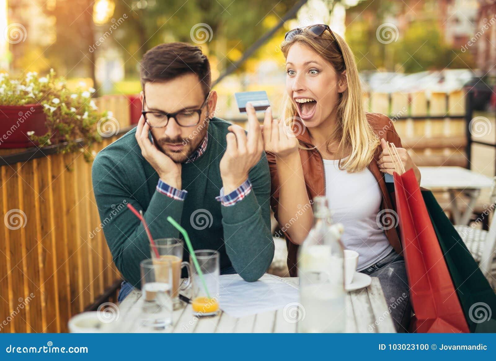 Kvinnasammanträde i kafé med den stiliga mannen och färgrika shoppingpåsar