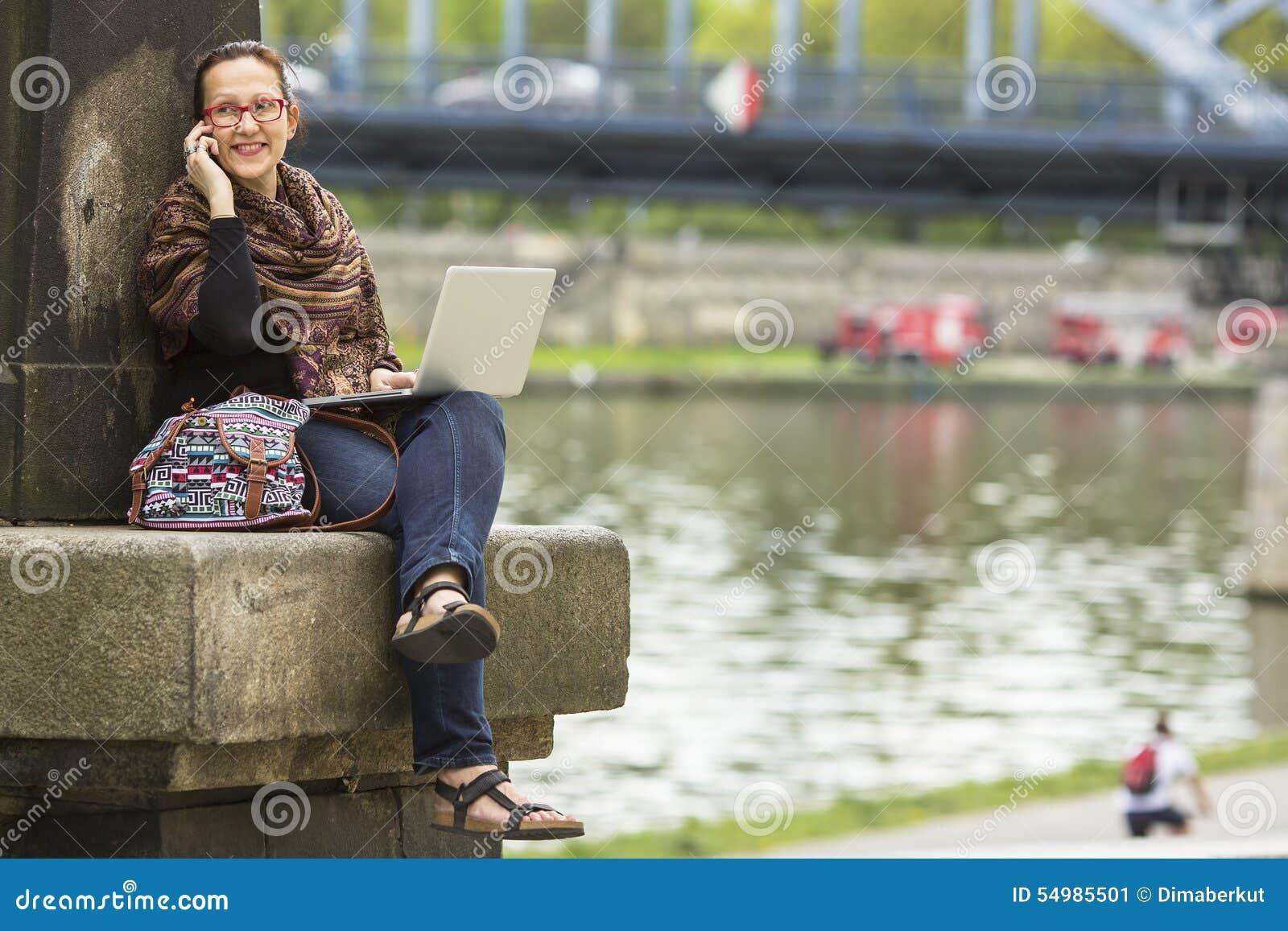Kvinnasammanträde med bärbara datorn på stranden av den gamla staden och samtal på telefonen freelancer