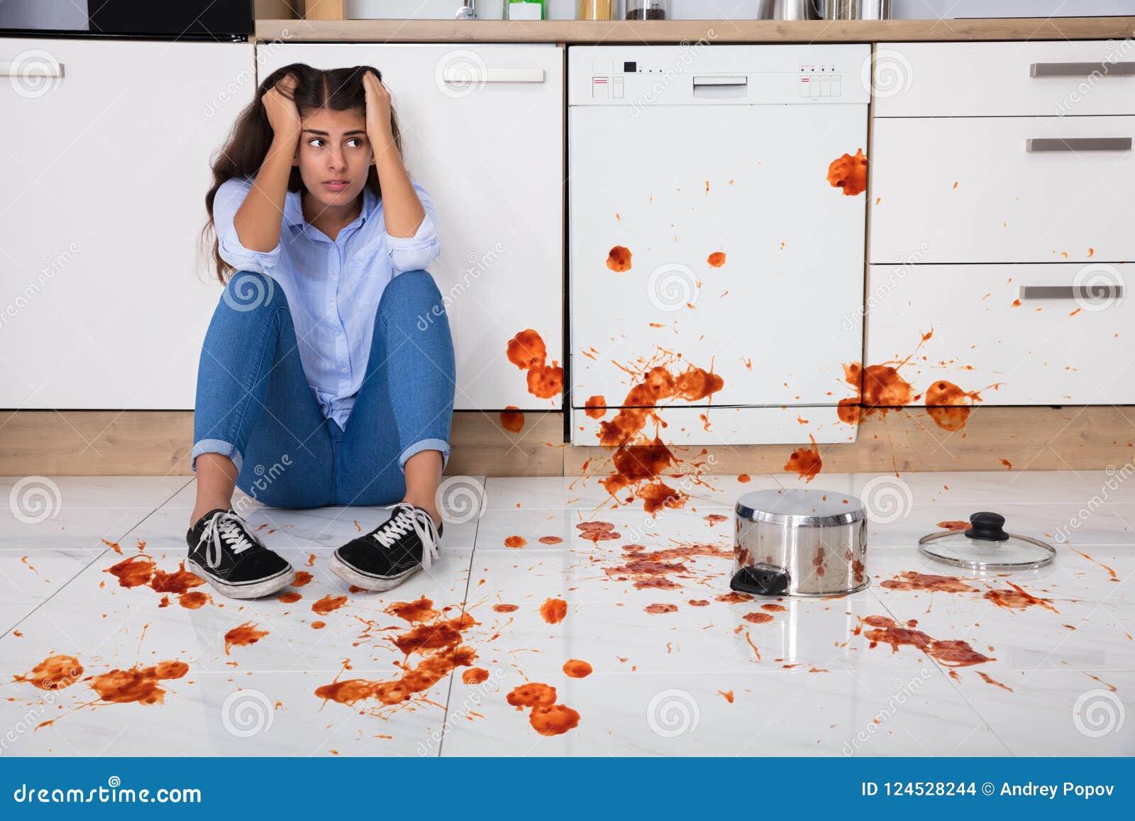 Kvinnasammanträde på kökgolv med spilld mat