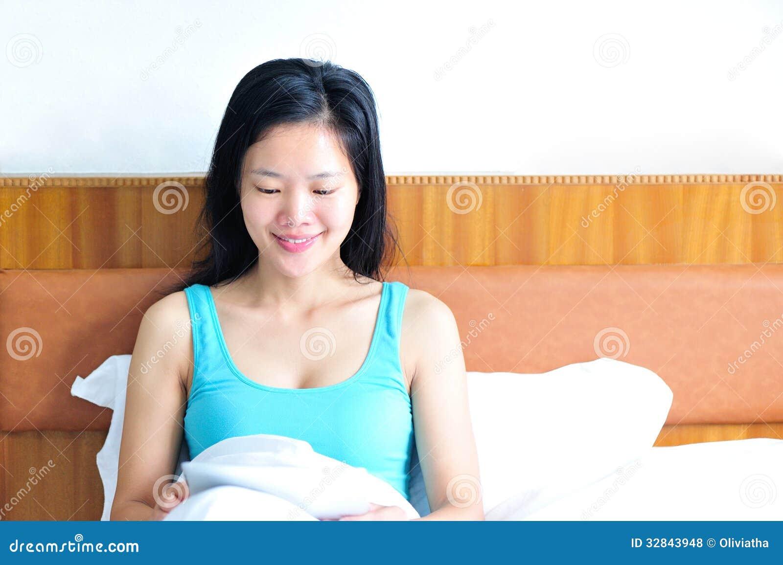 Kvinnasammanträde på sängen genom att använda hennes minnestavla