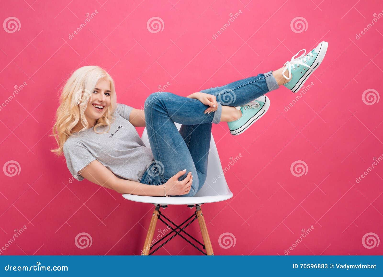 Kvinnasammanträde på stolen med lyftta ben