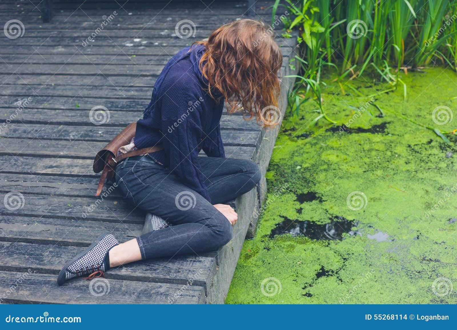 Kvinnasammanträde på trädäck vid dammet