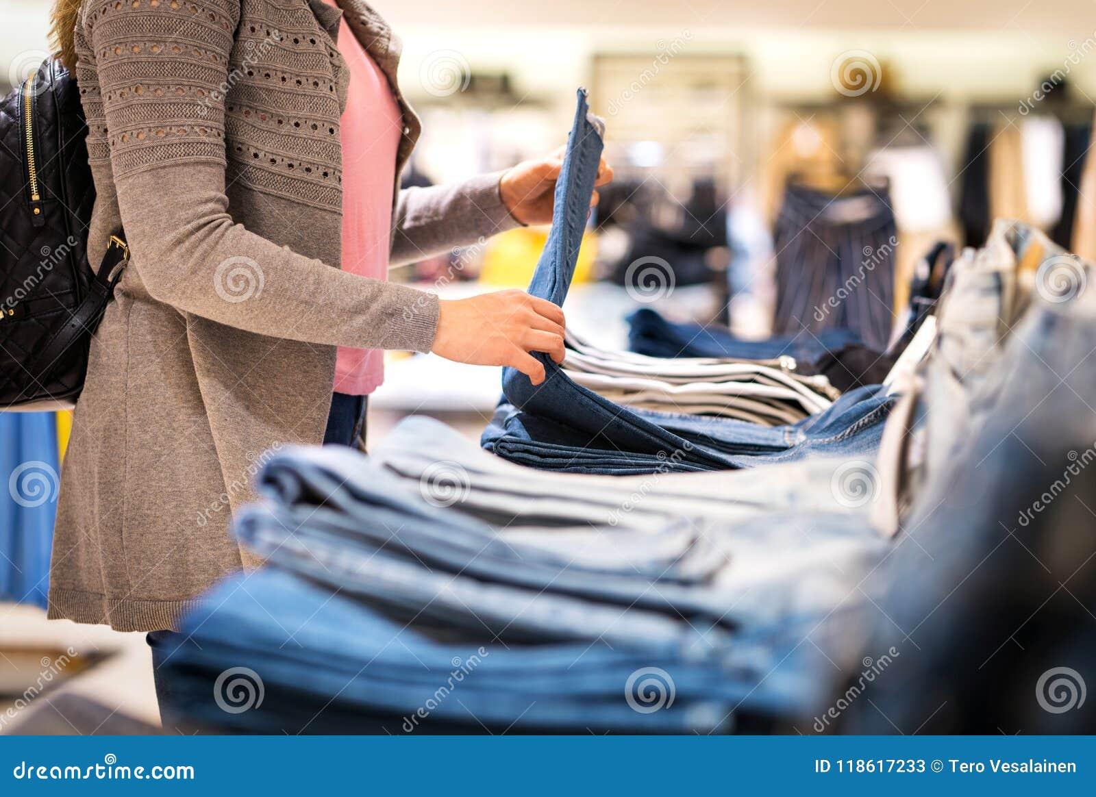 Kvinnashopping för jeans i modelager