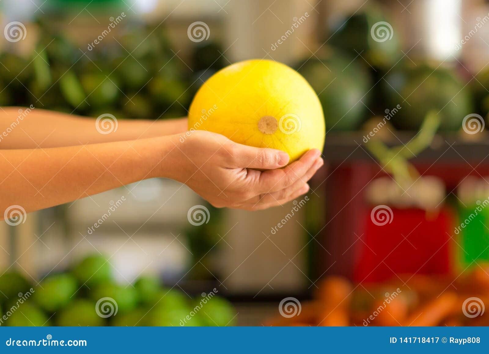 Kvinnashopping för sund frukt på en inomhus marknad shoppar