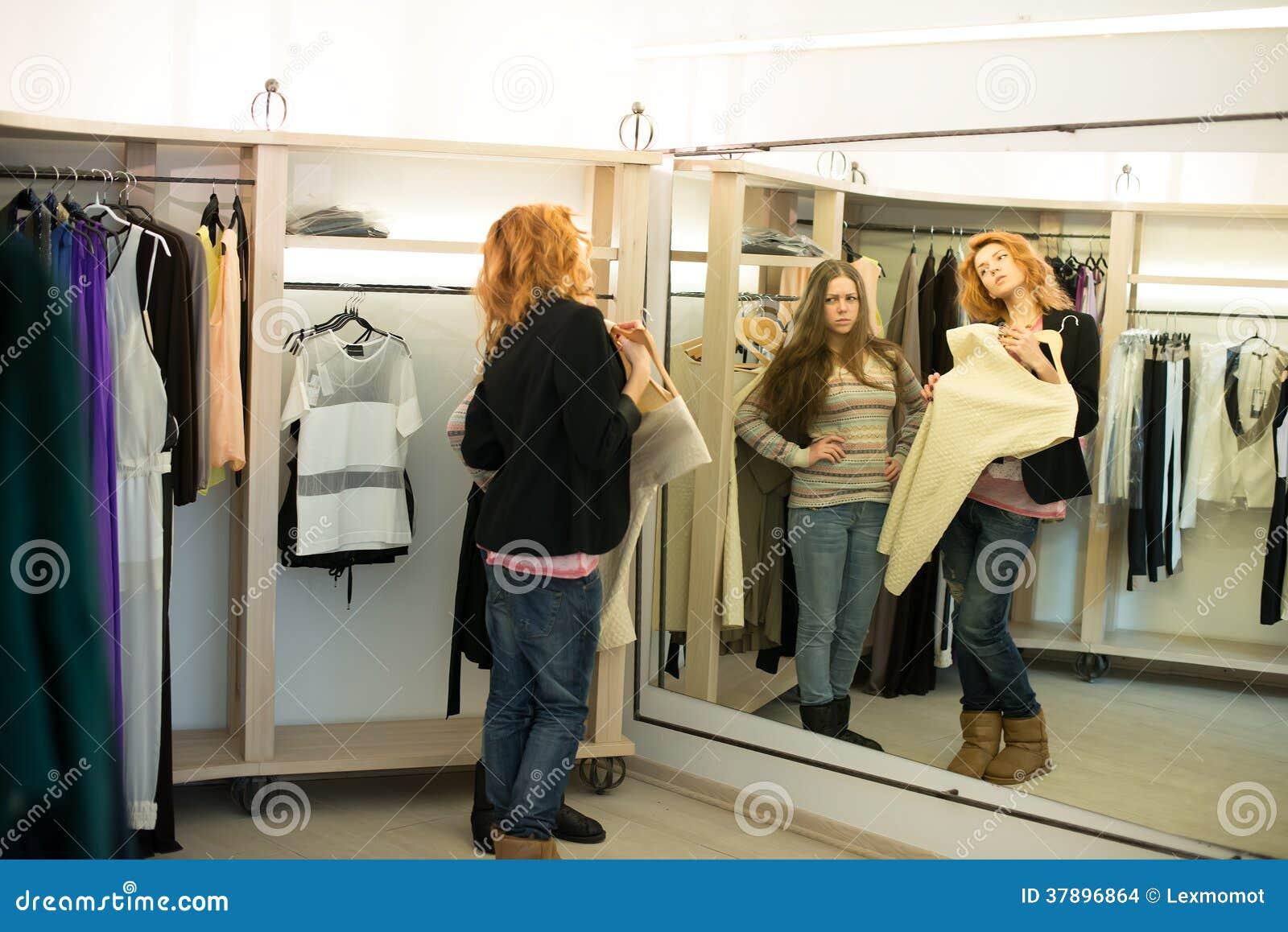 Kvinnashopping som väljer klänningar som ser i den osäkra spegeln