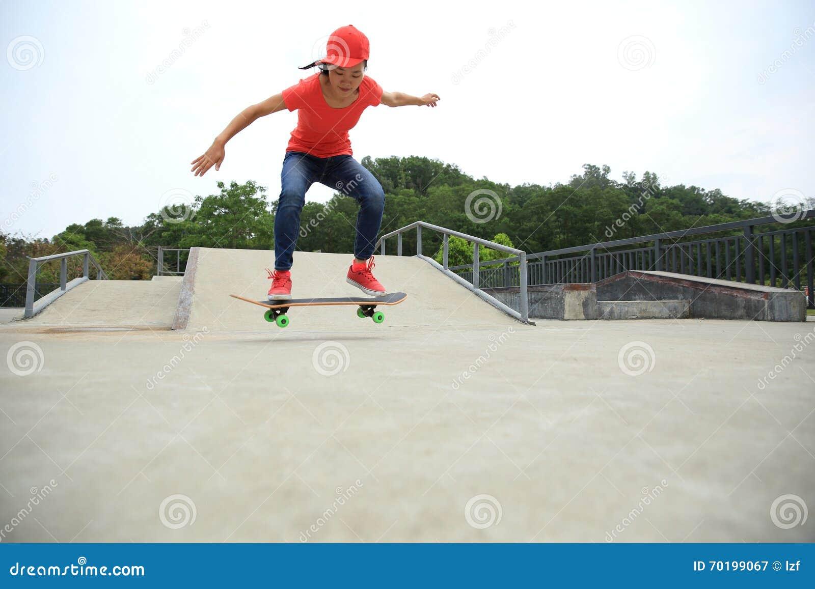 Kvinnaskateboarderen som skateboarding på skridskon, parkerar