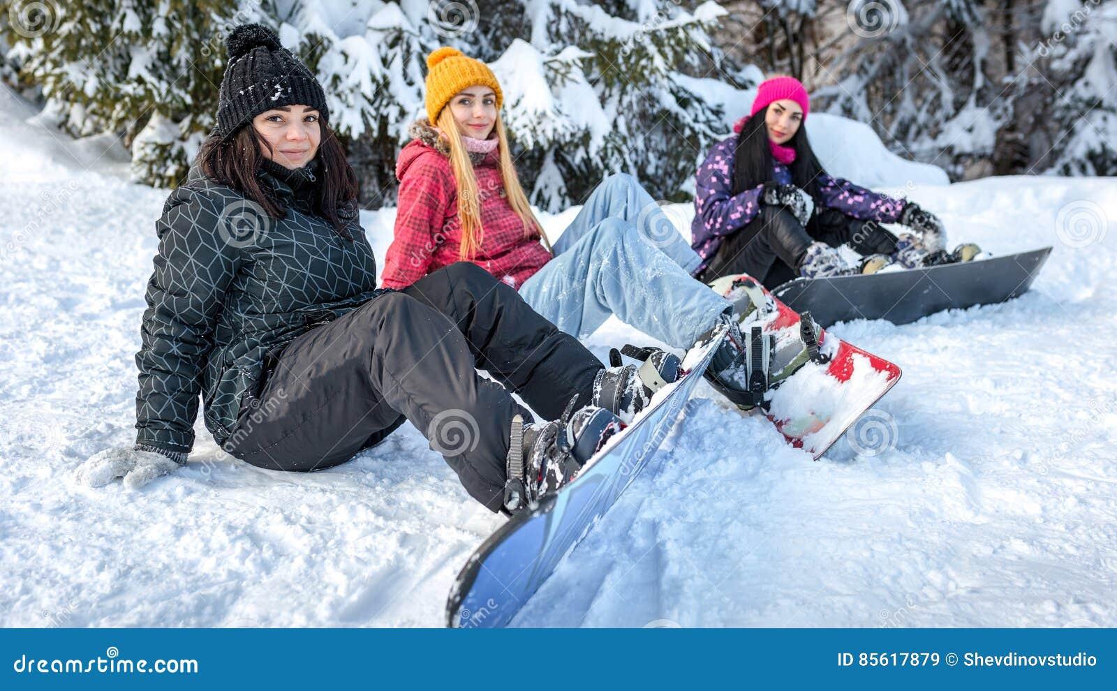 Kvinnasnowboarders som sitter på snön