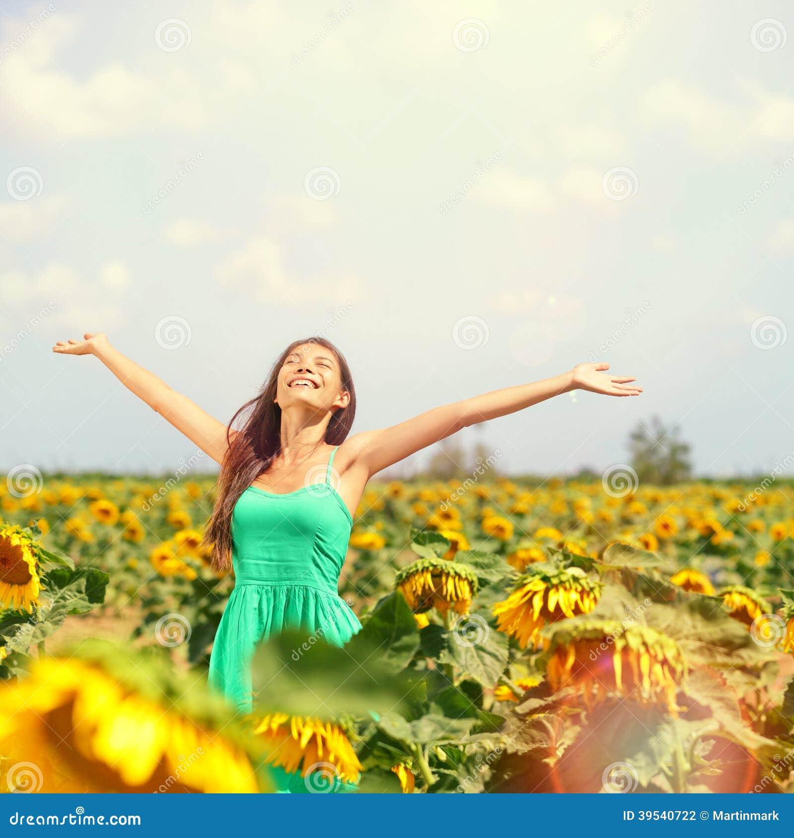 Kvinnasommarflicka som är lycklig i solrosblommafält