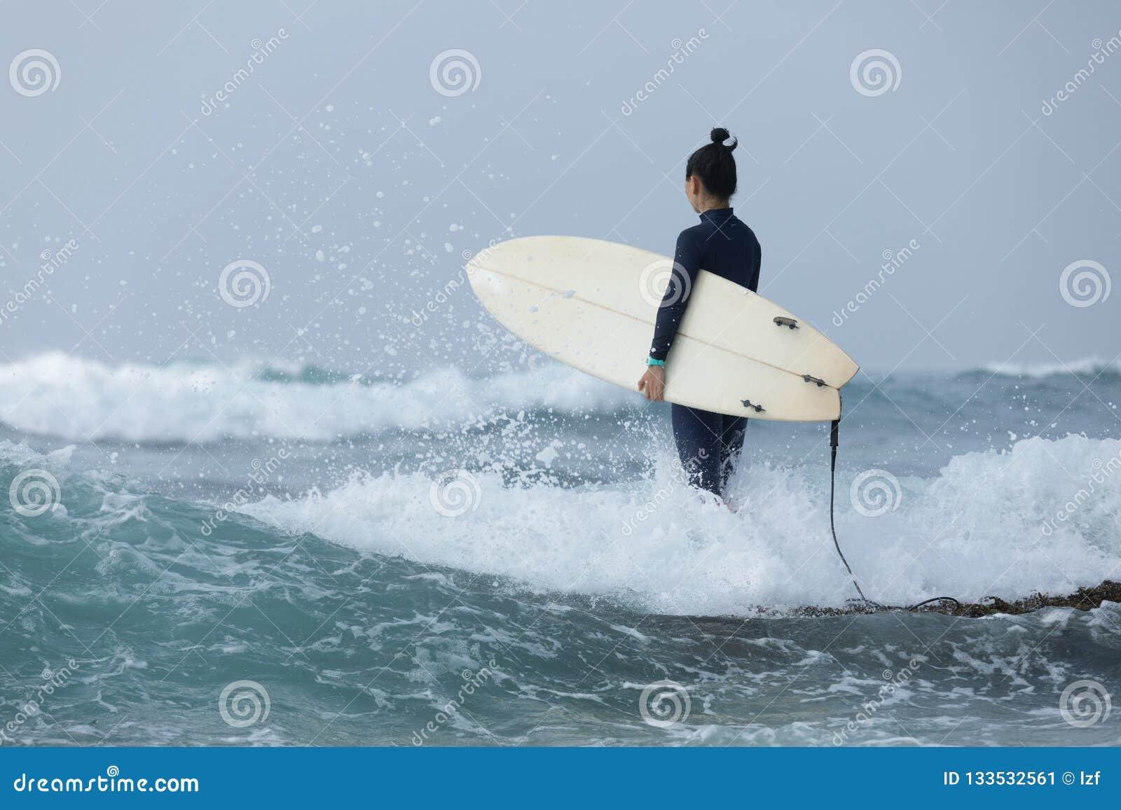 Kvinnasurfare med surfingbrädan