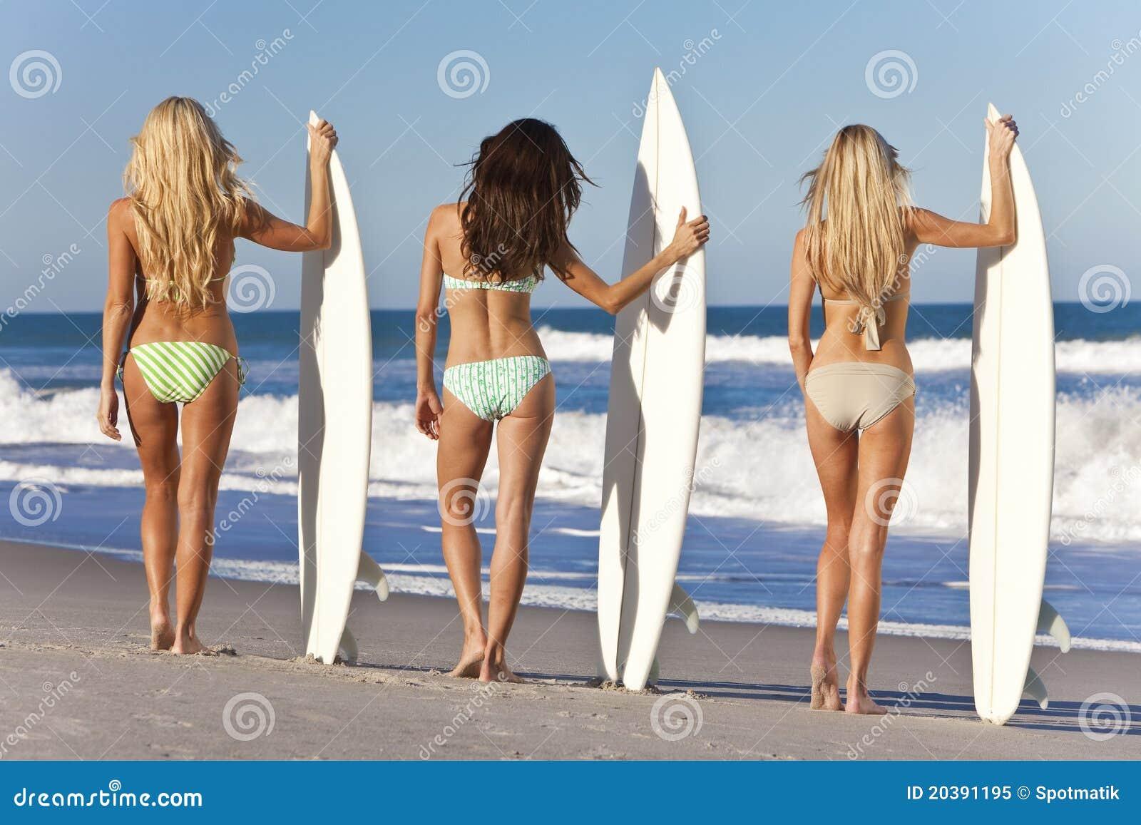 Kvinnasurfarear på bikinier med surfingbrädor på Beac