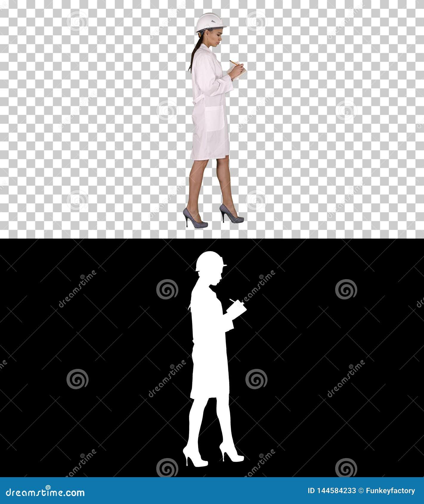 Kvinnateknikern med hjälmen är den rymmande pennan och kontrollistan som ner sätter något, medan gå, Alpha Channel
