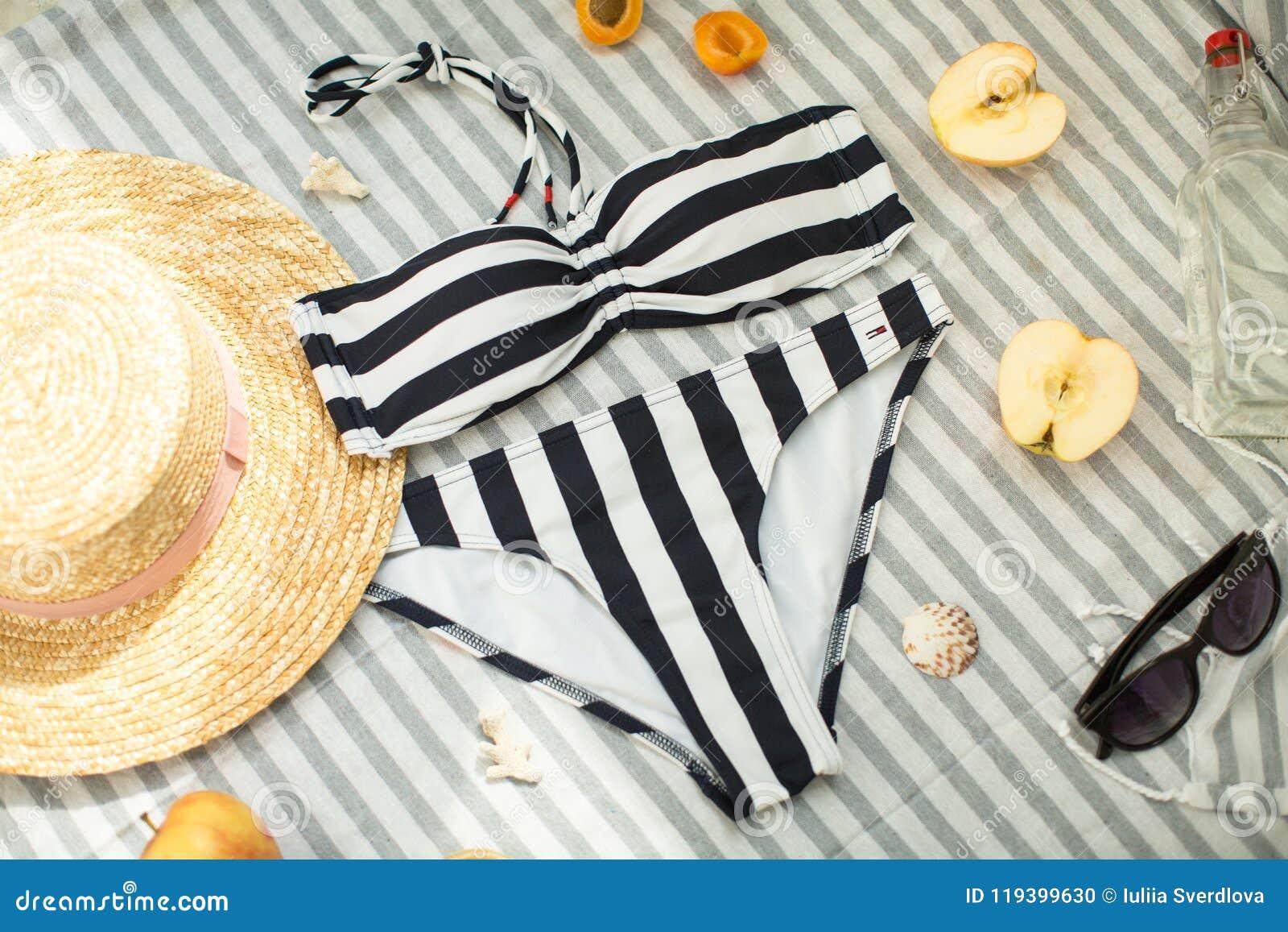 Kvinnatillbehör på stranden, baddräkten, hatten och exponeringsglasen