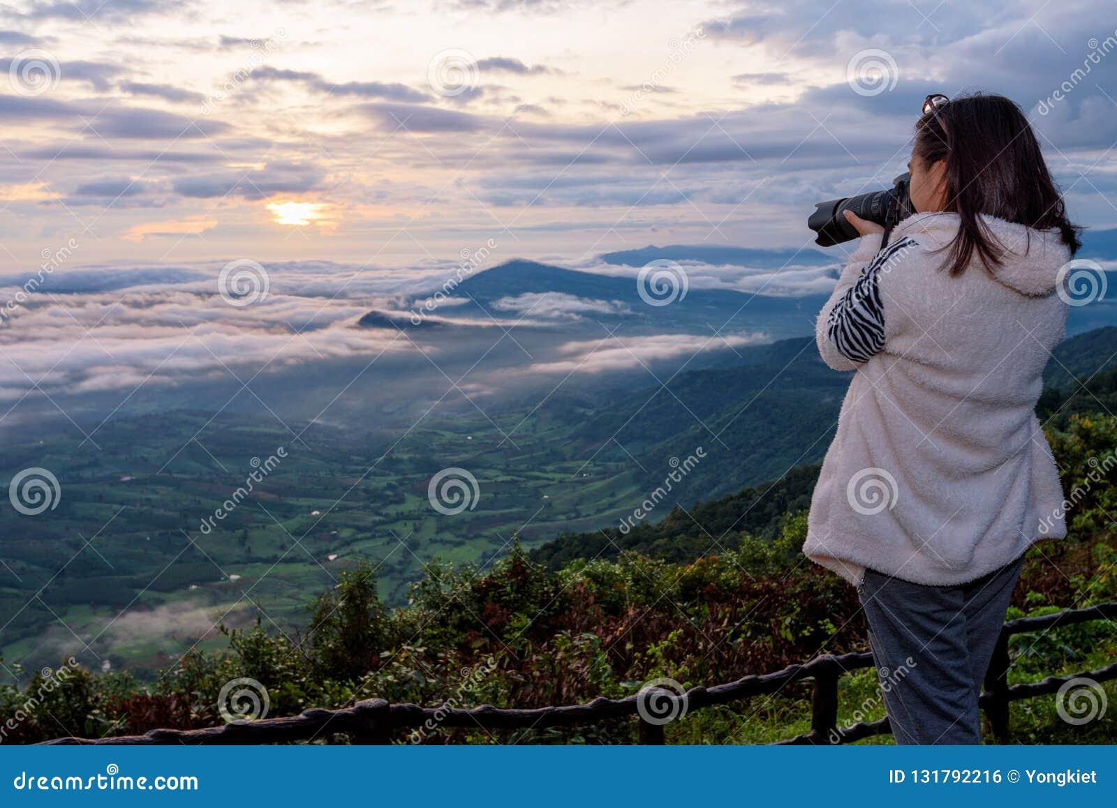 Kvinnaturisten använder en DSLR-kamera som fotograferar naturlandskap soldimmaberget i vintern under soluppgång på höjdpunkt