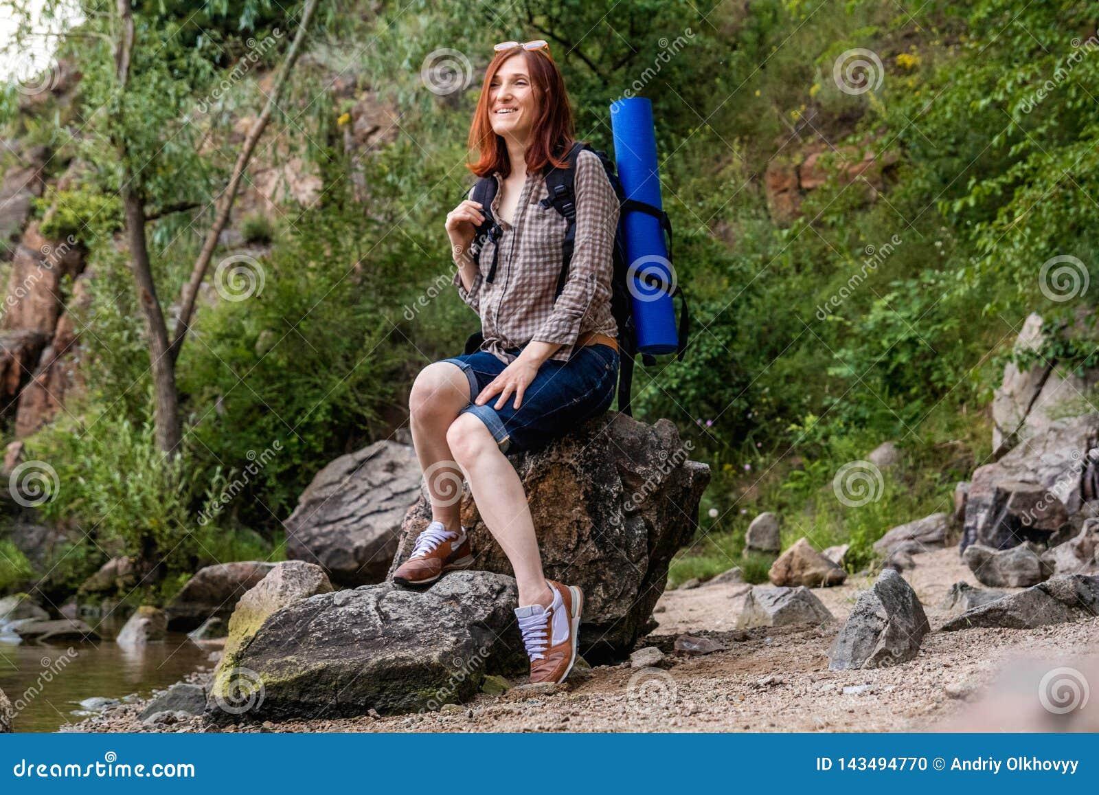 Kvinnaturisten med en ryggs?ck g?r i en vandring mot en bakgrund av h?rligt berglandskap l?ngs en bergflod