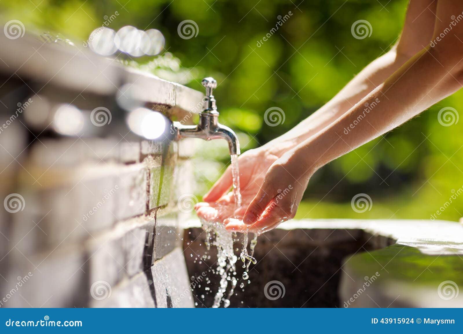Kvinnatvagninghänder i en stadsspringbrunn