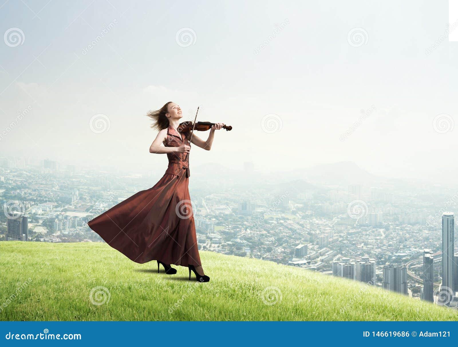 Kvinnaviolinist i den r?da kl?nningen som spelar melodi mot molnig himmel