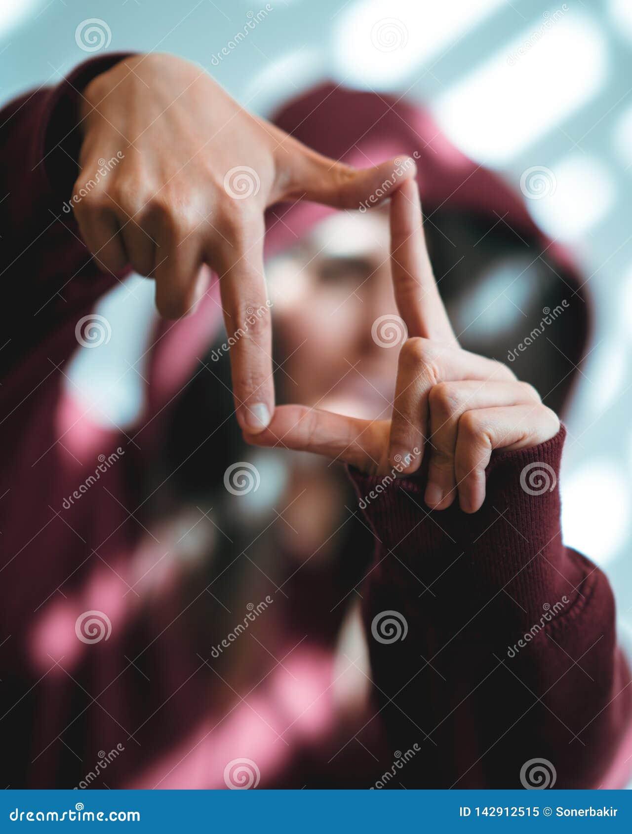 Kvinnavisning som inramar handgest på ljus bakgrund