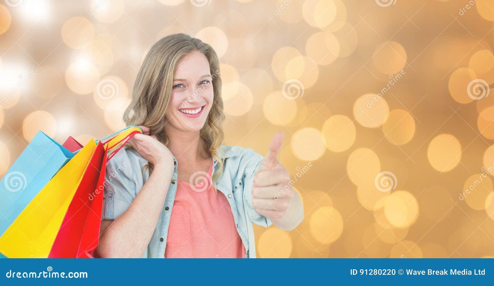 Kvinnavisningen tummar upp, medan rymma shoppingpåsar över bokeh