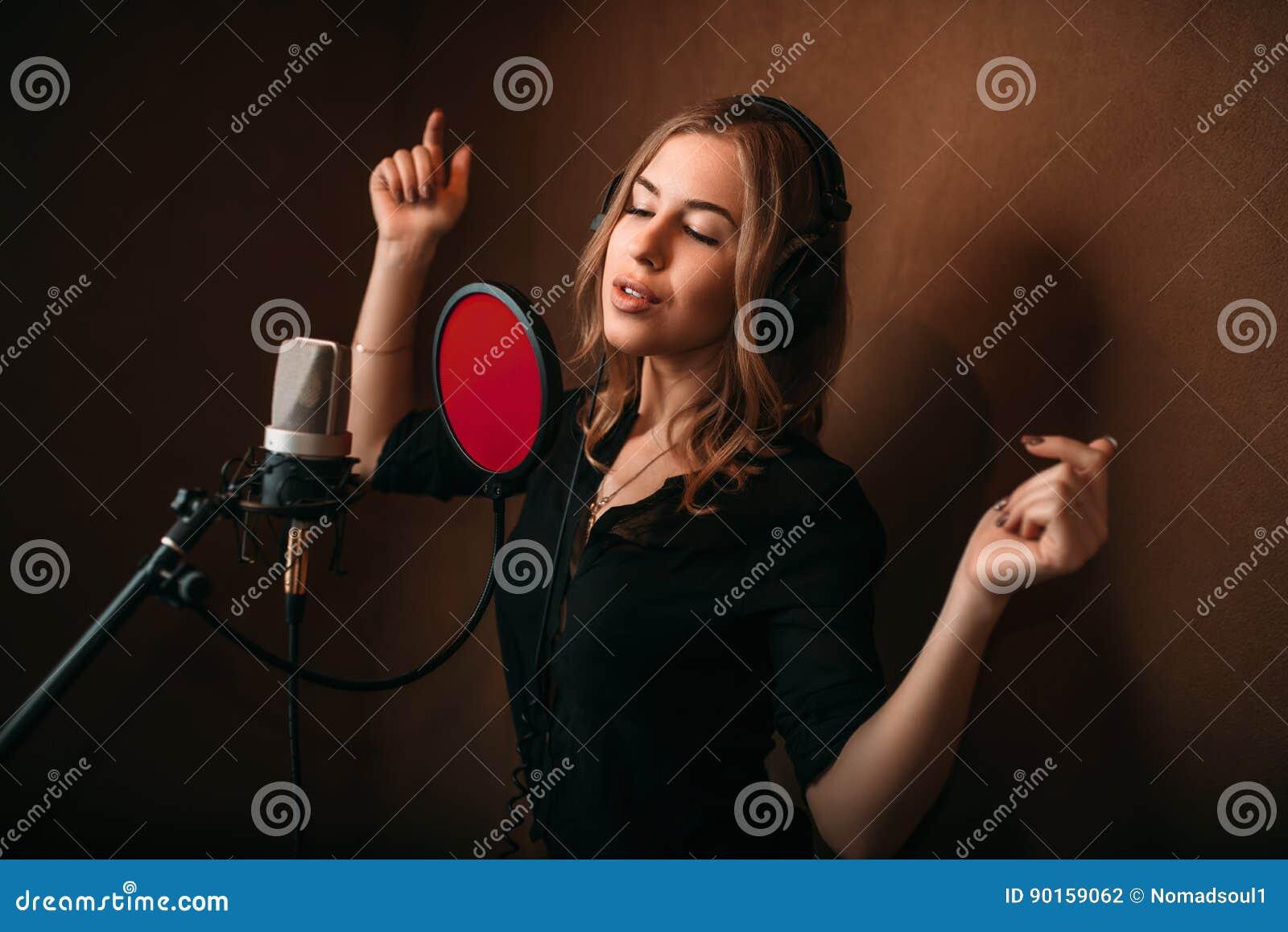 Kvinnavokalist i hörlurar mot mikrofonen