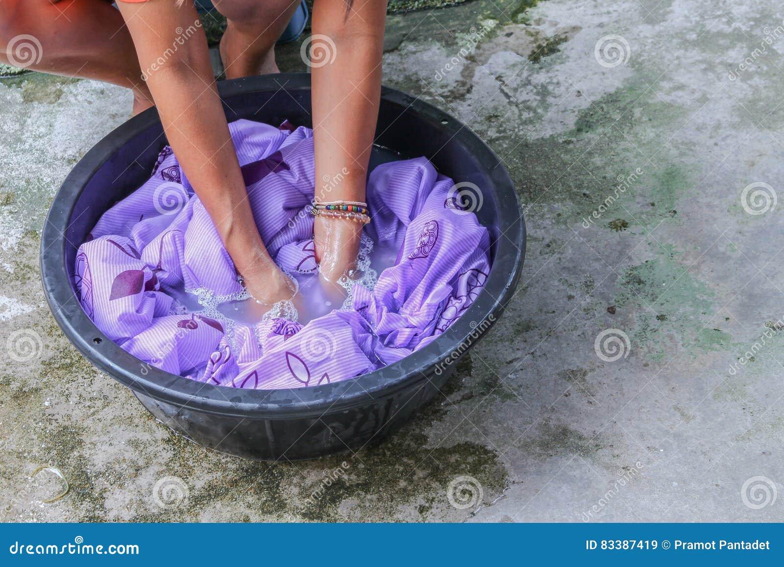 Kvinnawashhänder smutsar ner kläder i handfatsvarten för att rentvå