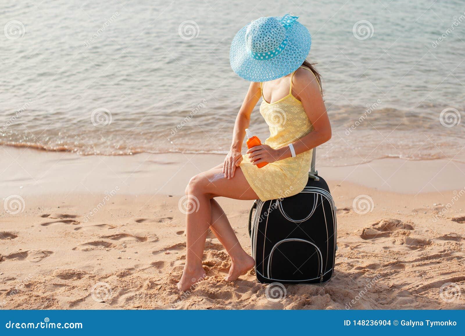 Kvinnlig applicerande solkräm på benet Skincare solskydd Kvinnasudd som fuktar lotionon på hennes släta brunbrända ben