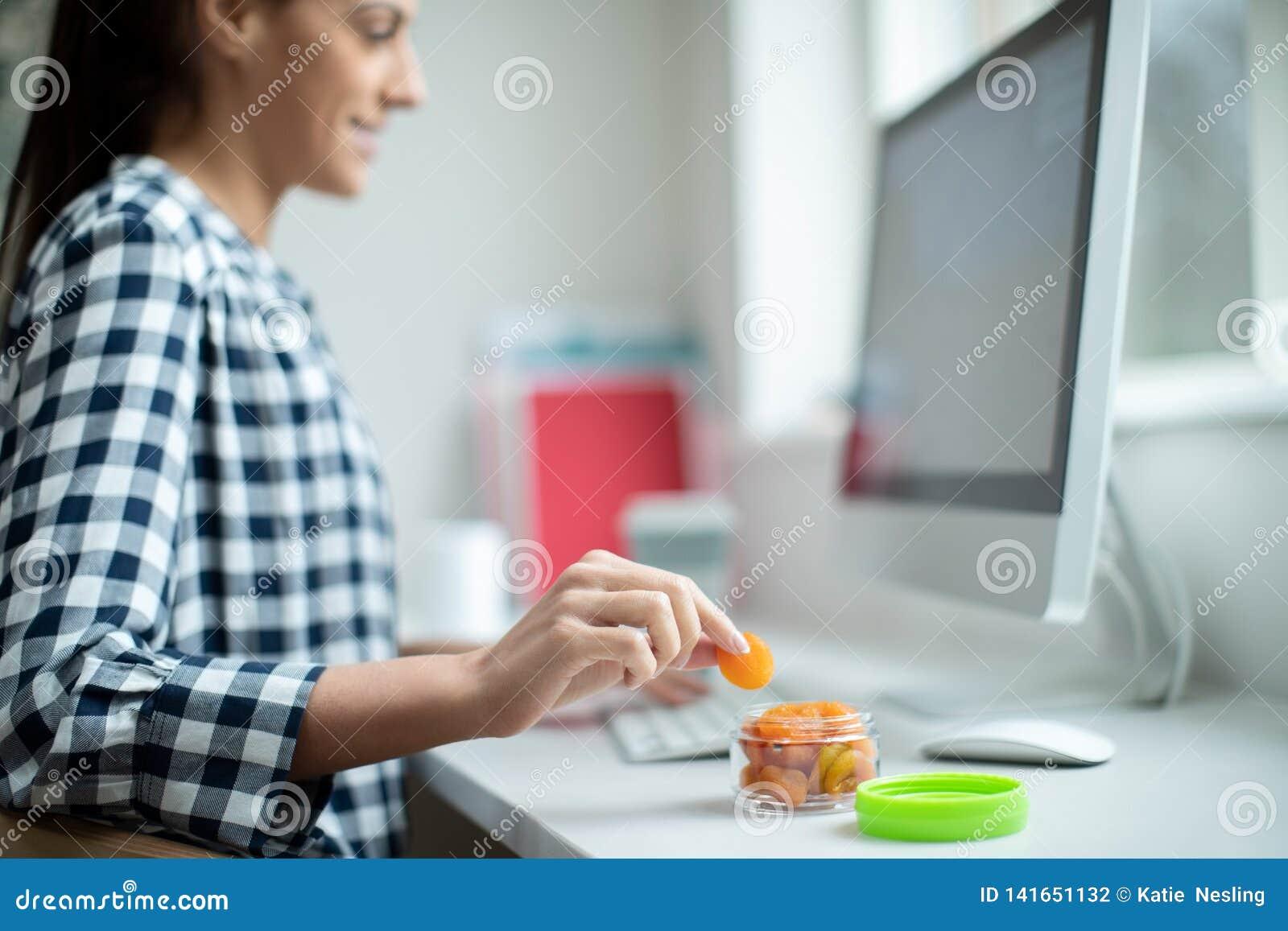 Kvinnlig arbetare i regeringsställning som har det sunda mellanmålet av torkade aprikors på skrivbordet