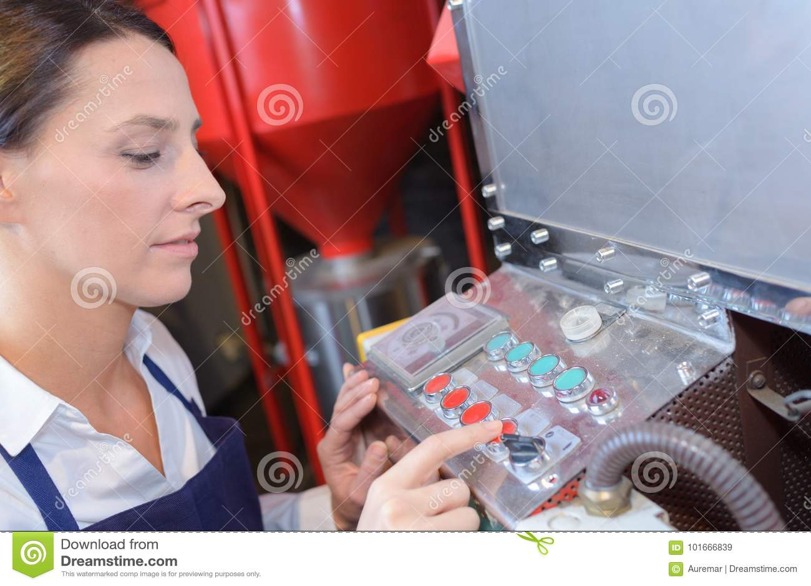 Kvinnlig arbetare som använder maskinen på fabriken