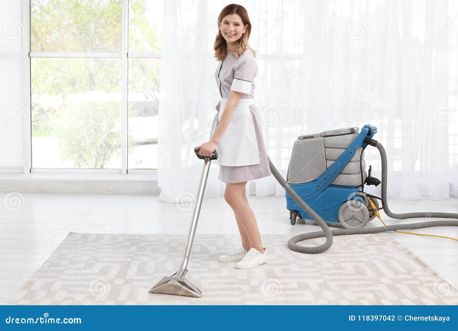 Kvinnlig arbetare som tar bort smuts från matta med yrkesmässig dammsugare, inomhus