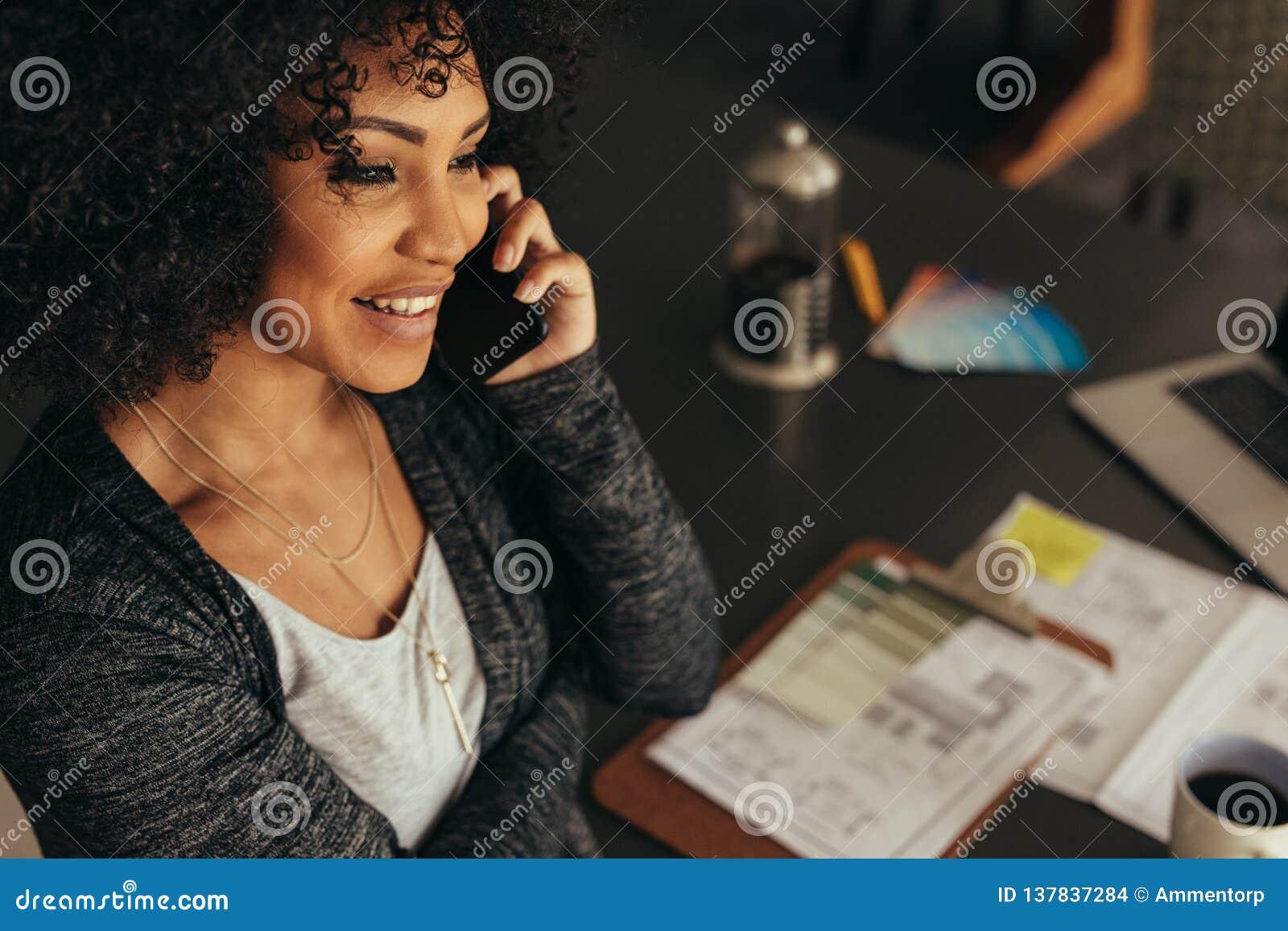 Kvinnlig arkitekt som talar med klienten över telefonen