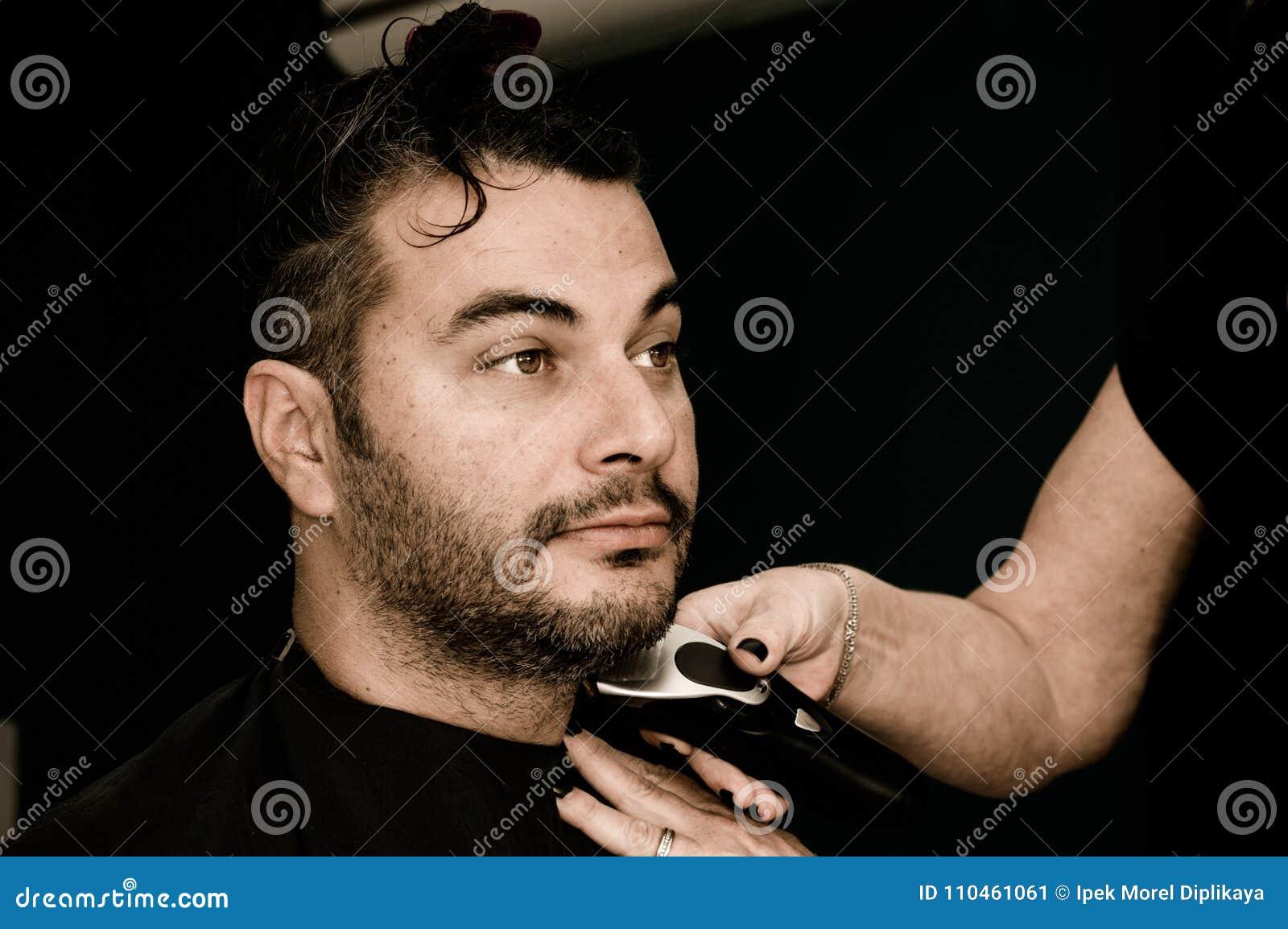 Kvinnlig barberare som arbetar med hårclipperen som rakar ung mans framsida