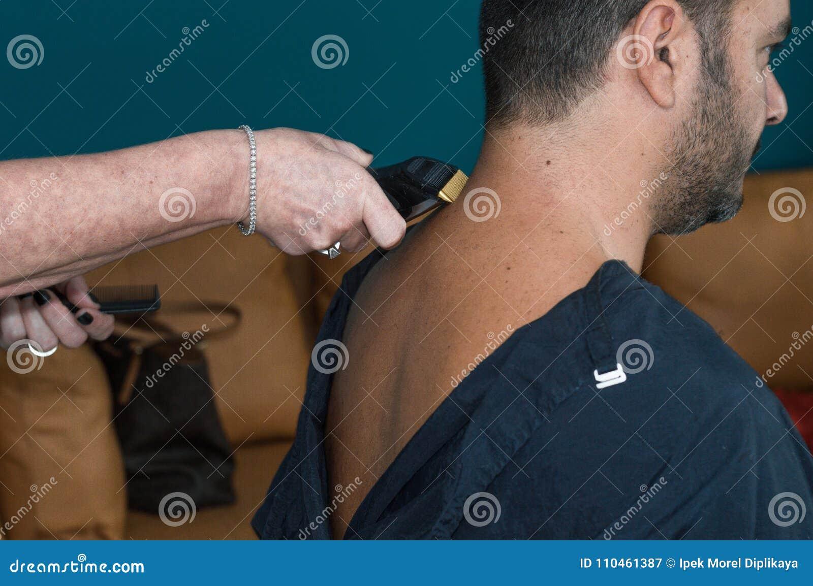 Kvinnlig barberare som arbetar med hårclipperen som rakar ung mans hals