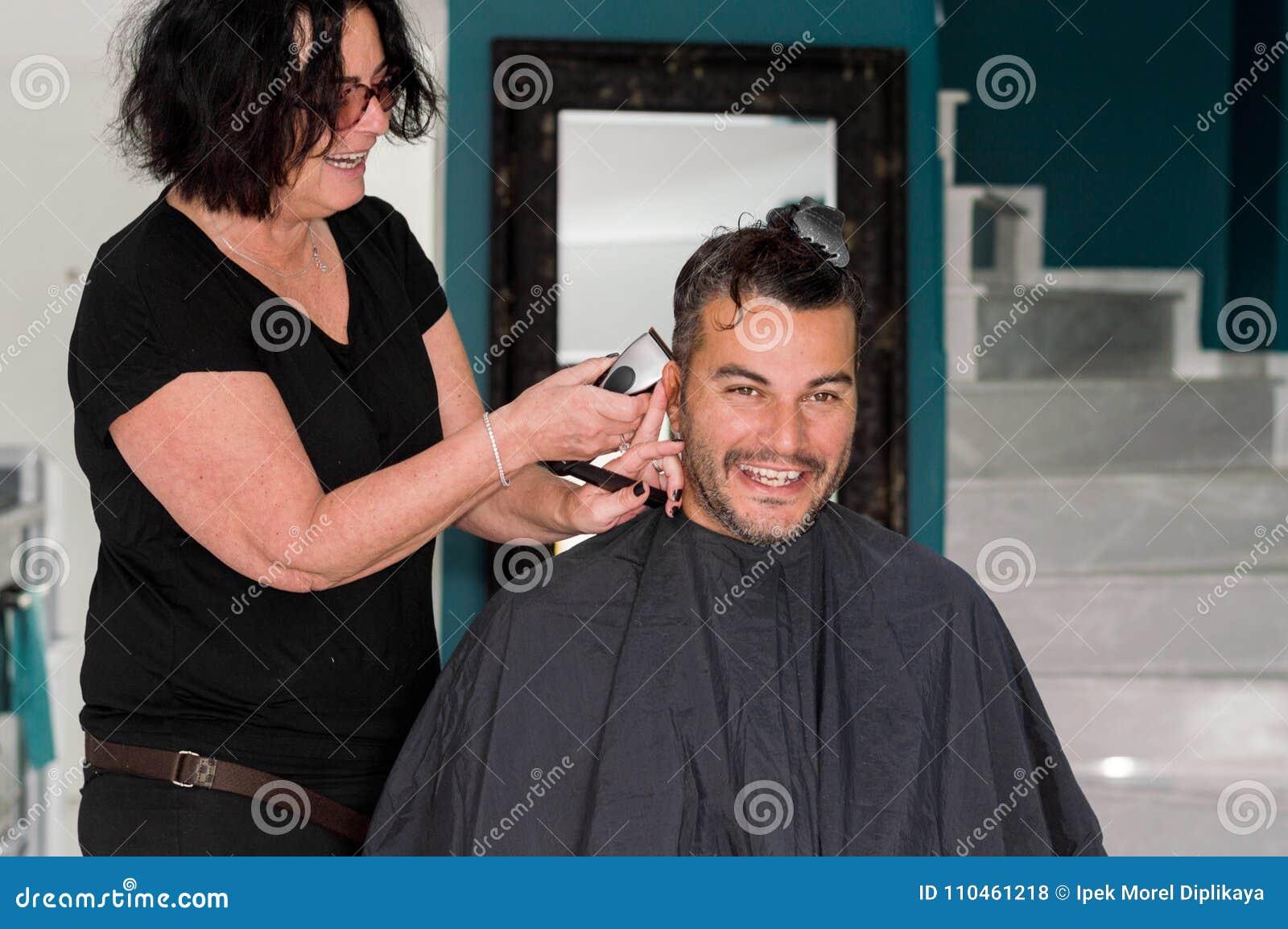 Kvinnlig barberare som arbetar med hårclipperen som rakar ung mans huvud