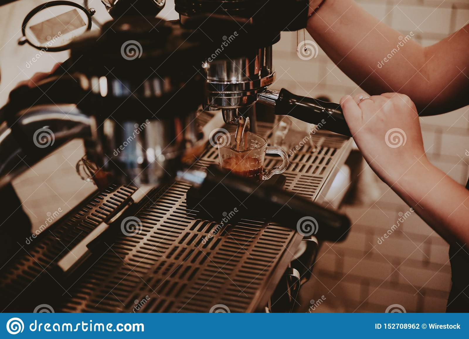 Kvinnlig barista genom att använda kaffemaskinen och göra en läcker latte