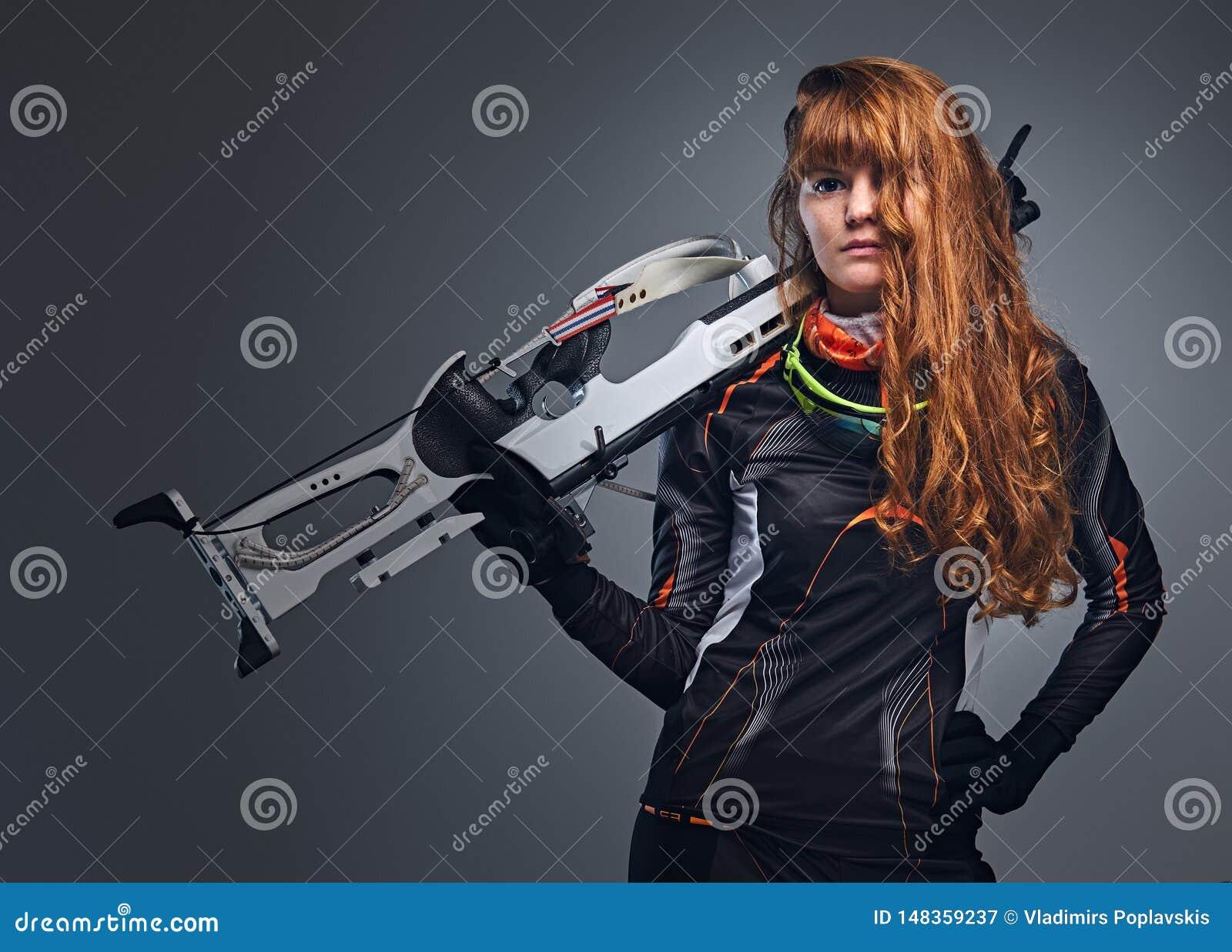 Kvinnlig Biathlonm?stare f?r r?dh?rig man som siktar med ett konkurrenskraftigt vapen