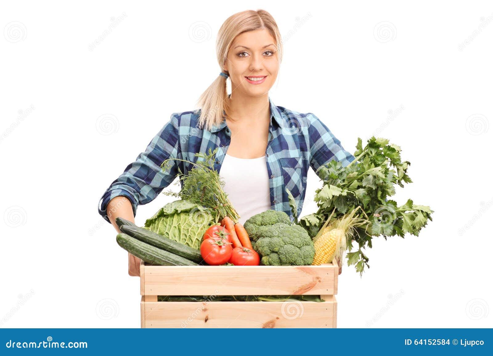 Kvinnlig bonde som poserar bak en spjällåda med grönsaker