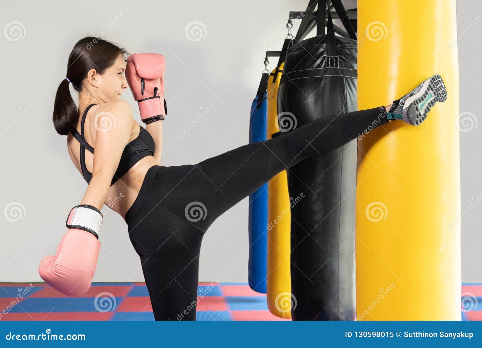 Kvinnlig boxare som slår en enorm stansa påse på en boxningstudio Kvinnaboxare som hårt utbildar Thailändsk boxarestansmaskinspar