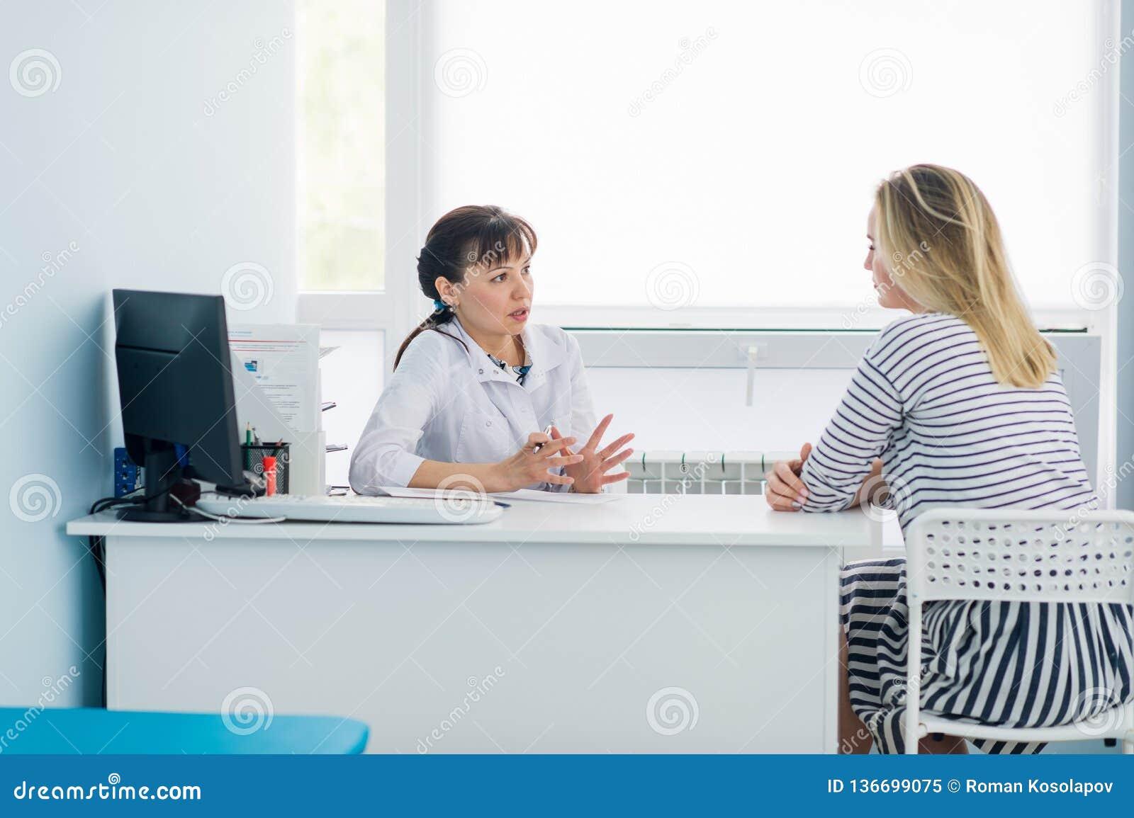 Kvinnlig doktor och patient som talar i sjukhuskontor Hälsovård och klientservice i medicin