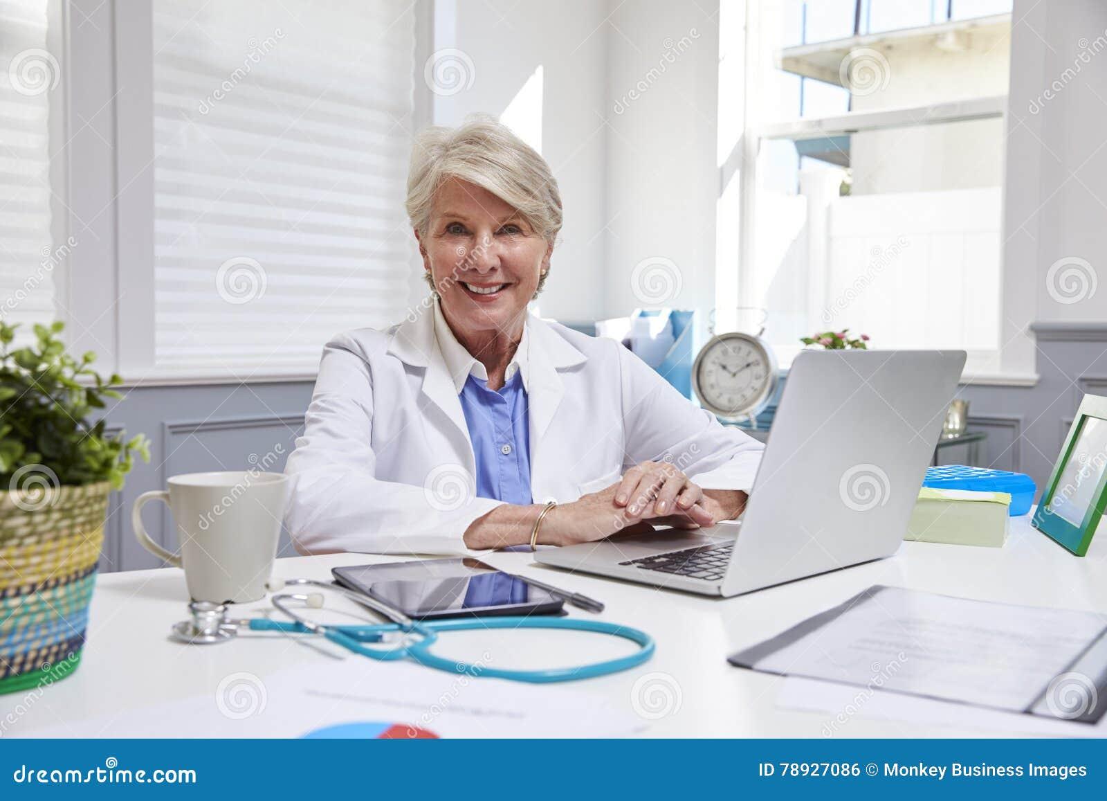 Kvinnlig doktor Sitting At Desk som i regeringsställning arbetar på bärbara datorn