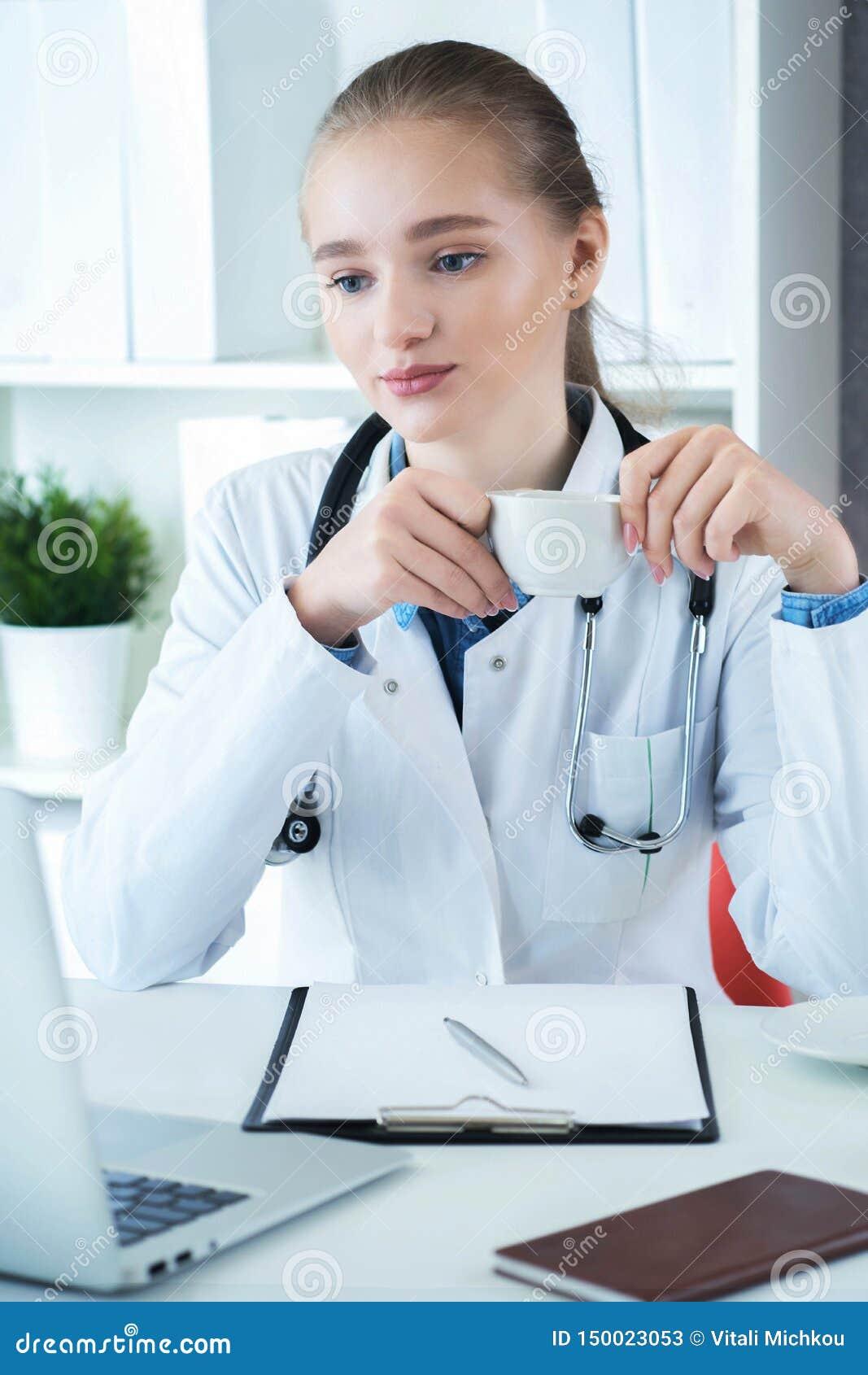 Kvinnlig doktor som arbetar på medicinskt sakkunskap- och drinkkaffe, medan sitta på skrivbordet framme av bärbara datorn Ung ter