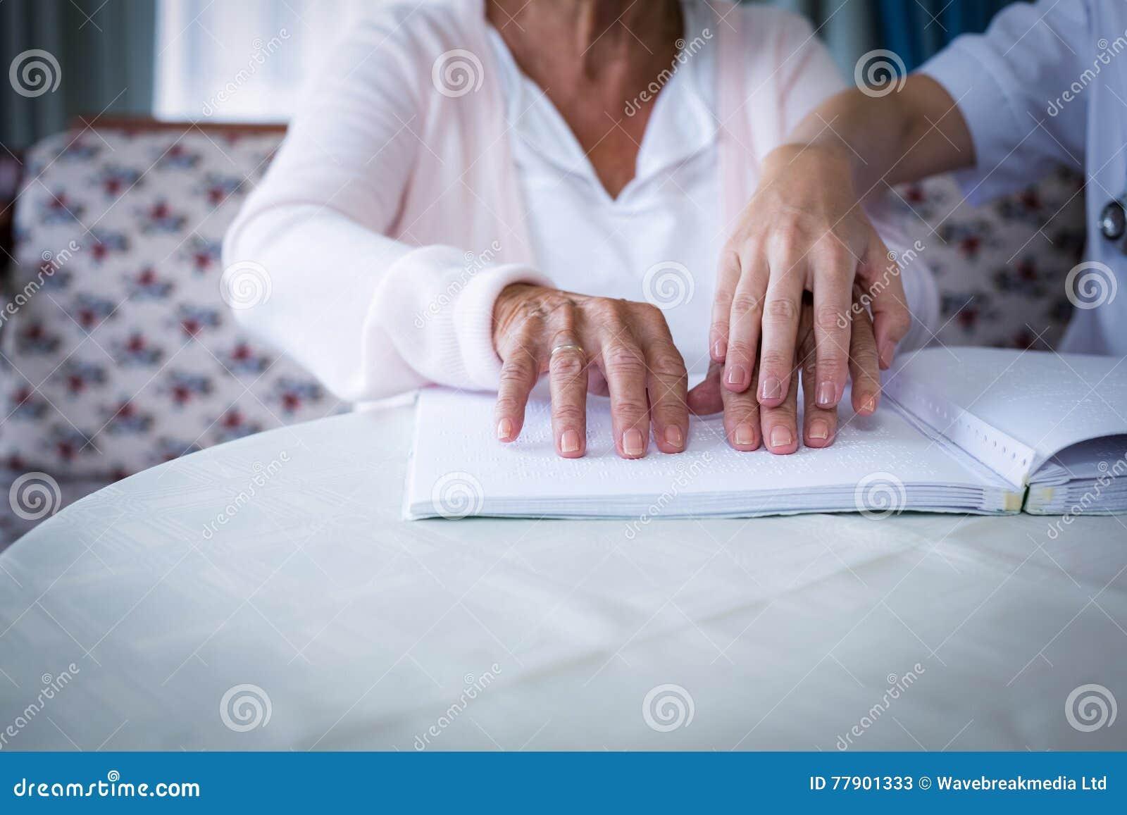 Kvinnlig doktor som hjälper en blind patient, i att läsa blindskriften för att boka