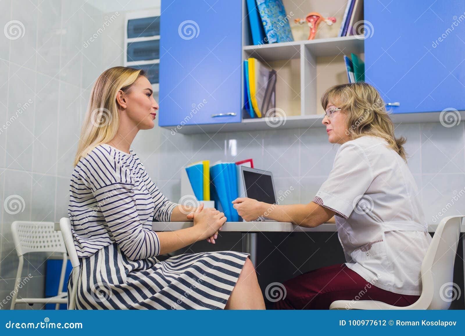 Kvinnlig doktor som talar med patienten i doktorskontor