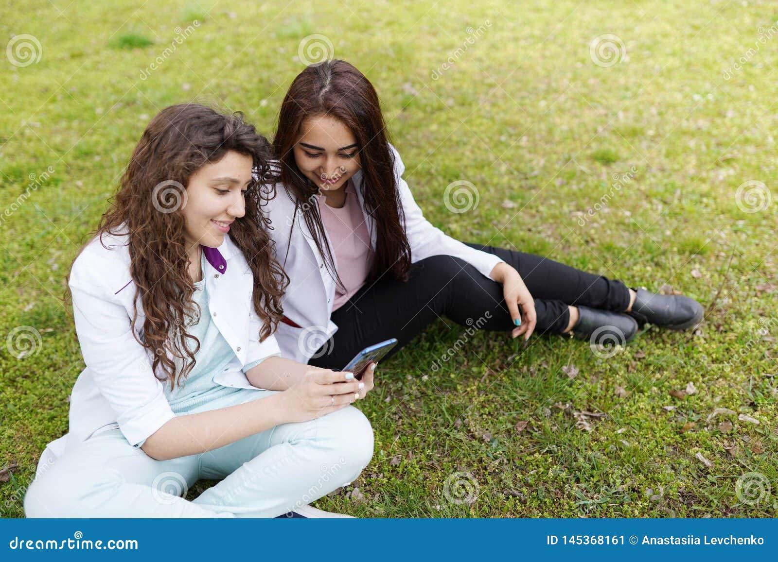 Kvinnlig doktorsstudent utomhus med telefonen optometriker f?r l?karunders?kning f?r bakgrundsdiagram?ga studenter n