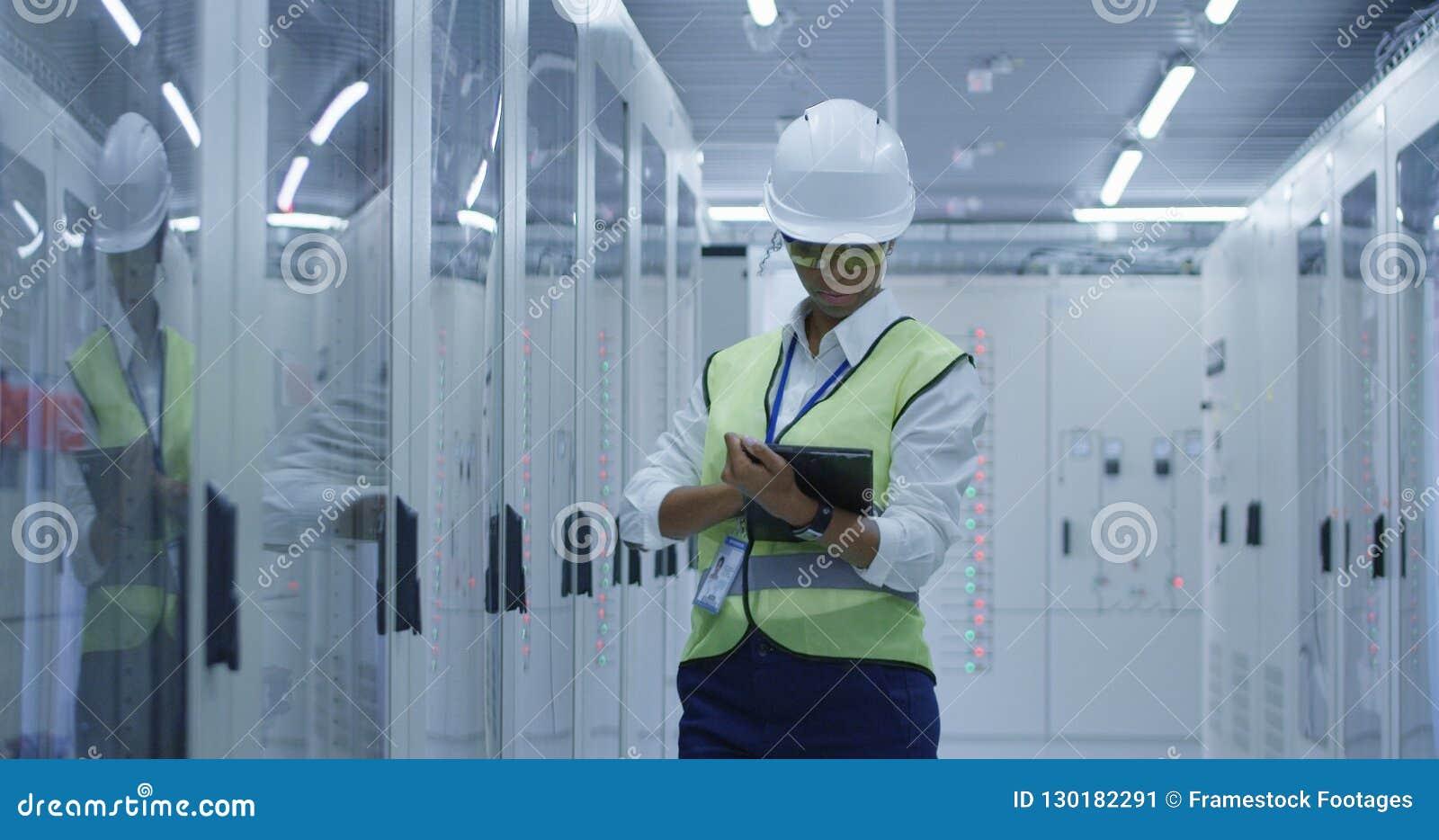 Kvinnlig elektrisk arbetare som utför en kontroll